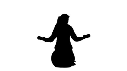 Silhouette of woman lifting dumbbells on exercise ball