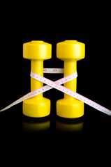 two yellow dumbbells and tape measure vertically on black backgr