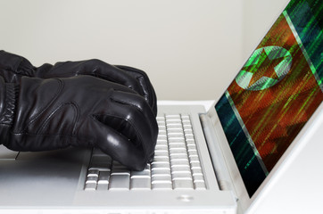Hacker wearing black gloves using a laptop with North Korea flag