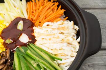 Korean cuisine, Bibimbap in  a clay pot on a wooden table