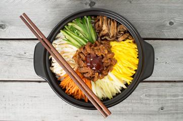 Korean cuisine, beef  Bibimbap in  a clay pot on wooden table
