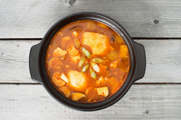 Korean traditional Kimchi soup in a clay pot against wood backgr