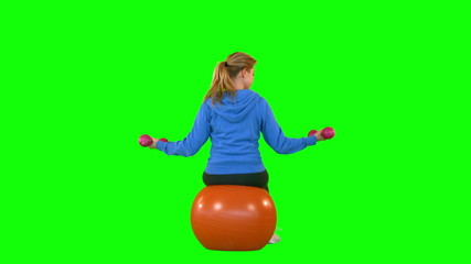 Rear view of fit woman with dumbbell sitting on exercise ball