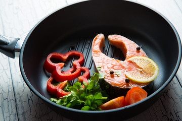 Fresh salmon steak in a pan grilled with vegetables