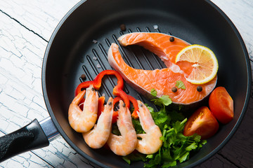 Fresh salmon steak in a pan grilled shrimp and vegetables