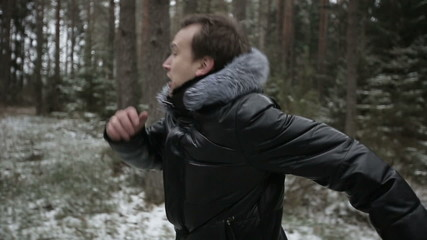 Two men running through the woods. Slow motion
