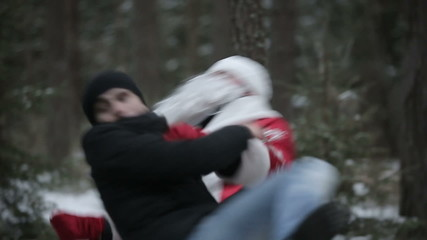 Santa Claus is fighting in the woods with robbers. Slow motion