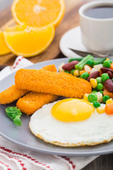 Fish sticks, fried egg and vegetables