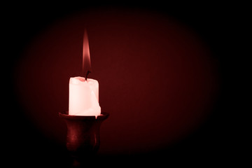 burning candle on a dark background. Tinted