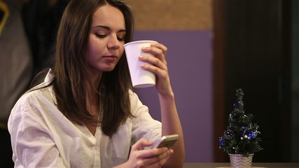 Young girl drinking coffee and writing sms greeting friends