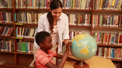 Cute pupil and teacher looking at globe