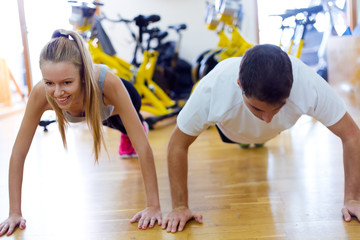 Young people doing exercise on the floor in the gym.