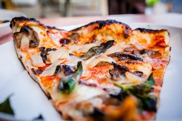 Slice of ham and mushroom pizza