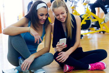 Young women using mobile phone in the gym.