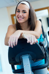 Young woman with elliptic machine in the gym.