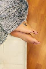Woman Feet on a Couch Covered with a Grey Blanket