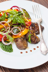 Warm salad with chicken liver, vegetables and lettuce