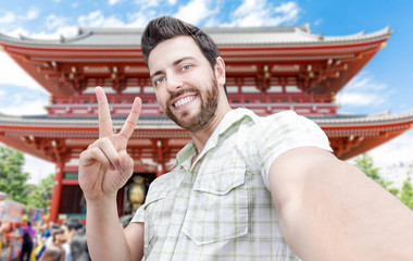 Happy young man taking a selfie photo in Tokyo, Japan