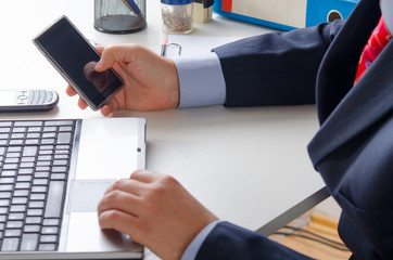 Businessman texting on the smart phone in the office