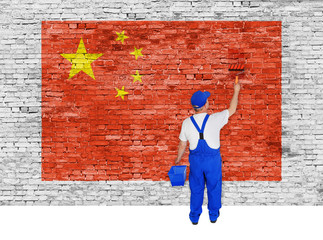 House painter covers brick wall with flag of China