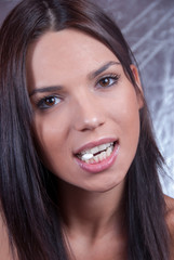 Young brunette woman pitt a pill with the teeths