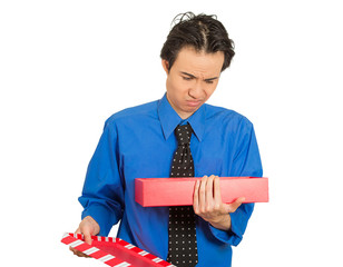 man opening gift box looking displeased at what he received