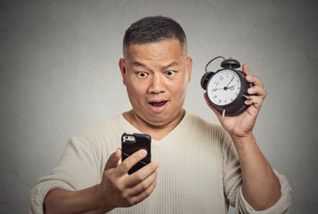surprised shocked man with alarm clock looking at smart phone
