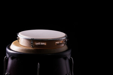 Tambourine laying on a bongo drum