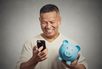 man employee holding piggy bank looking at smart phone