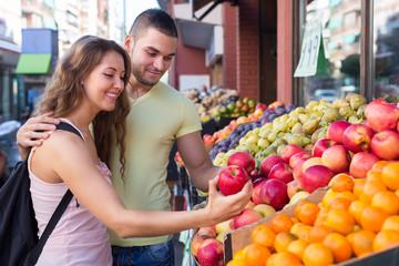 Happy couple picking fruits