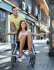 Husband taking spouse on wheelchair
