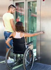 Couple with wheelchair in elevator
