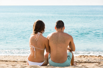 Happy pair relaxing on sand beach