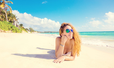 Happy young woman with sunglasses laying on beach.