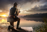 Young man fishing at misty sunrise