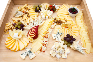 Mixed cheeses on a large light wooden board.