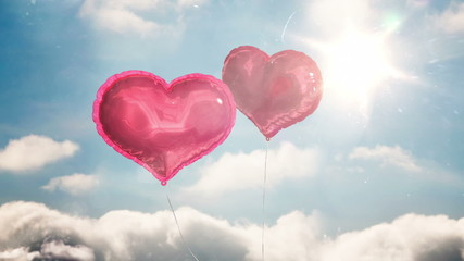 Heart balloons floating against blue sky