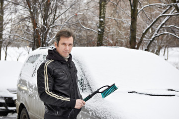 Driver of car with brush around in snow on winter