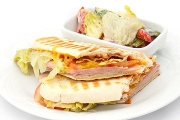 Cheese and ham panini with salad.
