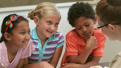 Teacher and pupils working at desk together