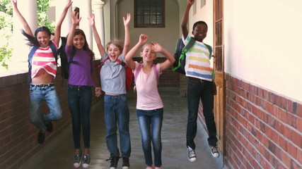 Happy pupils jumping in the air in a hallway