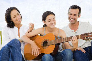Parents listening to their daughter playing guitar