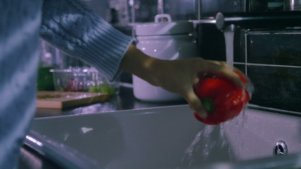 Woman's hands washing colourful peppers in slow motion