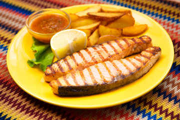 Grilled salmon steak with potatoes and sauce on a yellow plate