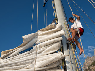 young man working on mast of sailing ship