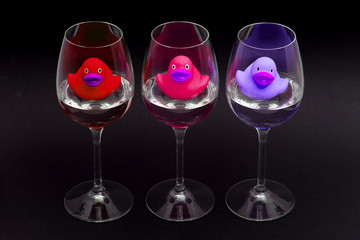 Red, pink and purple rubber ducks in wineglasses