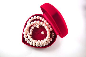 A necklace of pearls in a heart shaped red box