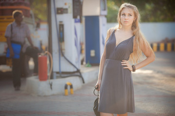 blonde girl in gray dress stand on petrol station