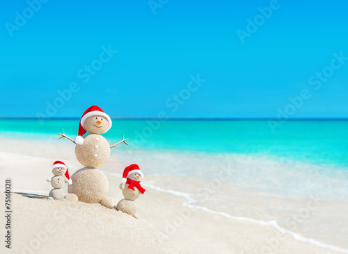 Snowmen family at tropical beach in santa hats. New Years and Ch - 75160328