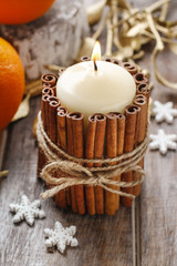 Candle decorated with cinnamon sticks, christmas decoration